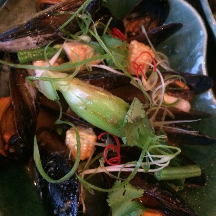 A serving of mussels steamed in bourbon and served in a chowder-esque broth with wood-fired corn.