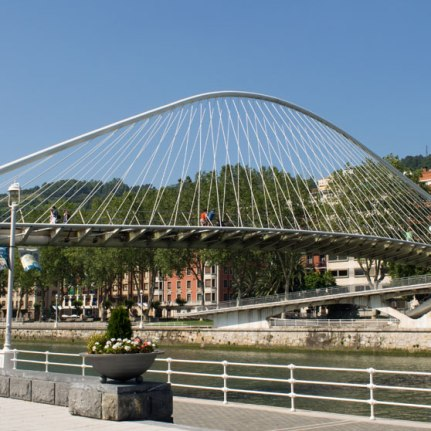 """Inaugurated in 1997 and designed by the famous Spanish architect Santiago Calatrava, this modern bridge, together with the Guggenheim Museum, became the symbol of the """"new"""" Bilbao. As its name indicates, the bridge is white (""""zubi"""" means bridge and """"zuri"""" white in Basque) and features a glass floor. It is characterized by its curvature, which together with the arch, creates a beautiful and interesting structure."""