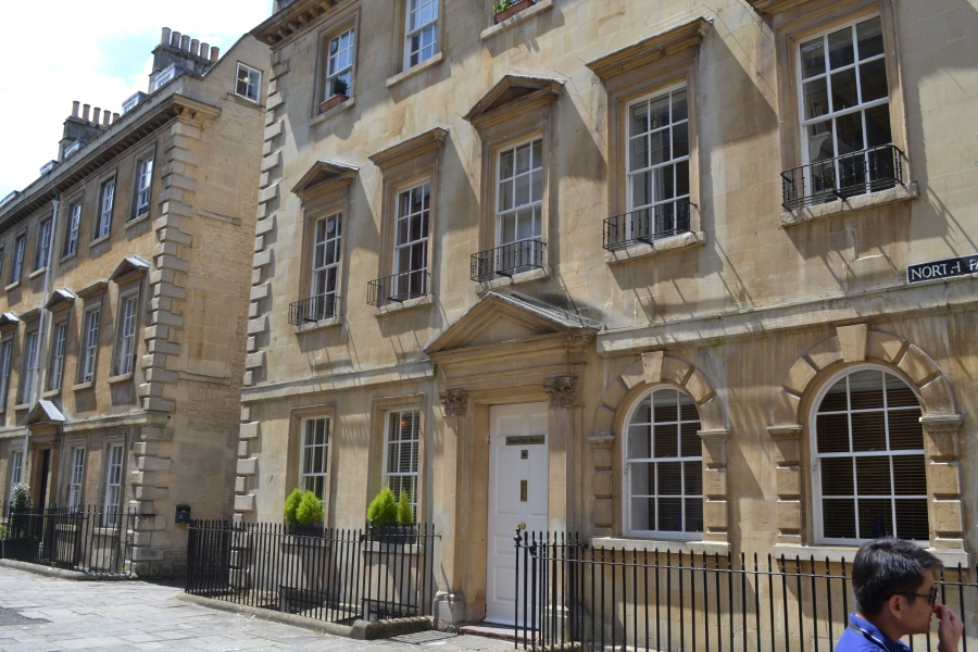 """Most of Bath's buildings are made from the local, golden-coloured, Bath Stone. The dominant architectural style is Georgian,[8] which evolved from the Palladian revival style that became popular in the early 18th century. The city became a fashionable and popular spa and social centre during the 18th century. Based initially around its hot springs, this led to a demand for substantial homes and guest houses. The key architects, John Wood and his son, laid out many of the city's present-day squares and crescents within a green valley and the surrounding hills. According to UNESCO this provided... """"an integration of architecture, urban design, and landscape setting, and the deliberate creation of a beautiful city""""."""
