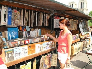 """Browsing through vintage prints and books of Les Boquinistes. Installed along more than three kilometres of the Seine and declared a UNESCO World Heritage site, the 240 bouquinistes make use of 900 """"green boxes"""" to house old books, antique journals, stamps and trading cards."""